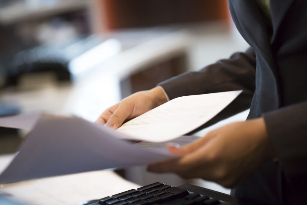 Woman is holding business documents in the office, close up, selective focus
